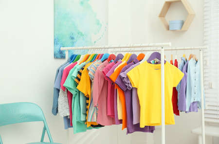 Different child's clothes hanging on racks in room