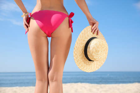 Young woman with beautiful body on beach, closeup