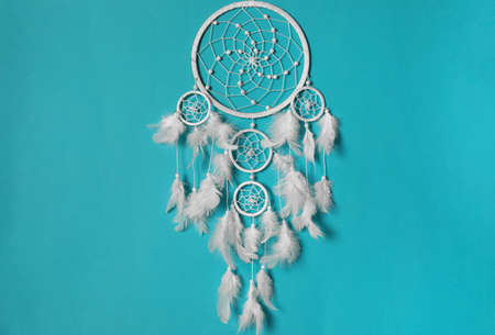 Beautiful dream catcher hanging on light blue background