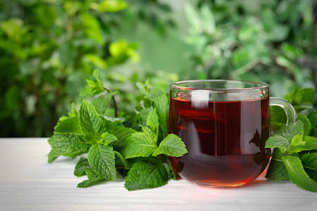 Fresh tea with mint leaves on white wooden table Stock Photo