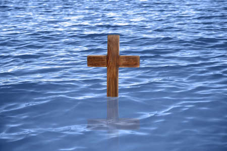 Wooden cross in river for religious ritual known as baptism Foto de archivo