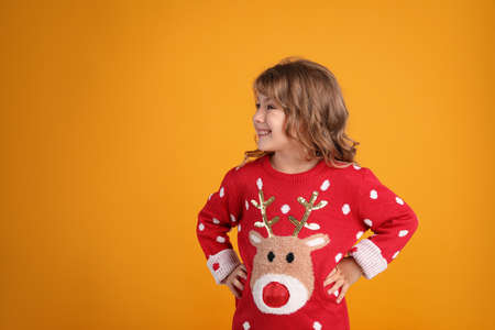 Cute little girl in red Christmas sweater smiling against orange background. Space for text