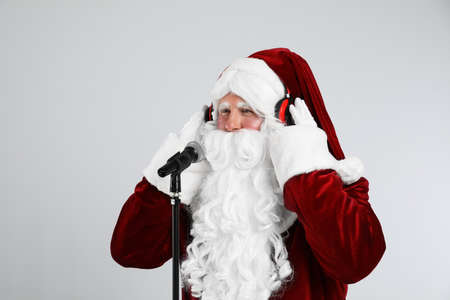 Santa Claus with headphones and microphone on light gray background. Christmas music