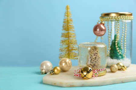Handmade snow globe and Christmas decorations on light blue background, space for text Stock Photo