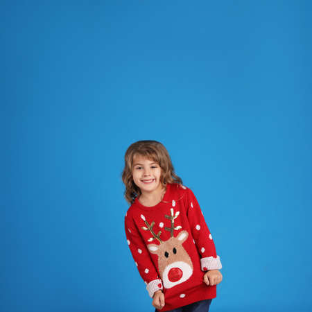 Cute little girl in red Christmas sweater smiling against blue background Stock Photo