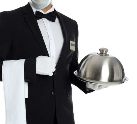 Waiter in medical mask holding tray with lid on white background, closeup