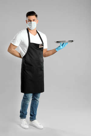 Waiter in medical face mask with empty tray on light gray background