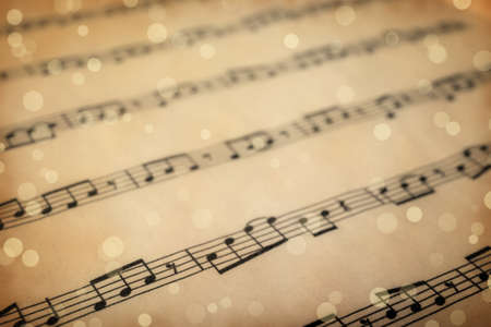 Old sheet with Christmas music notes as background, bokeh effect