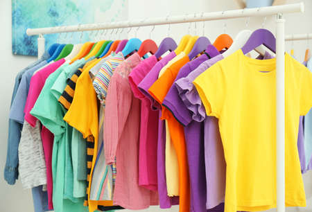 Different child's clothes hanging on rack in room Stockfoto