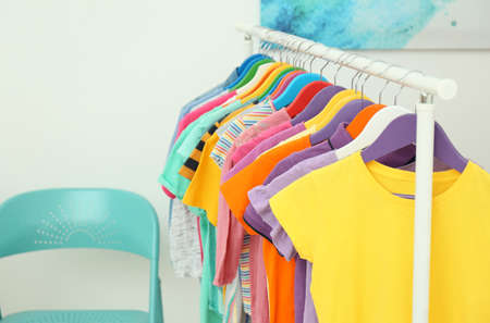 Different child's clothes hanging on rack indoors. Space for text Stockfoto