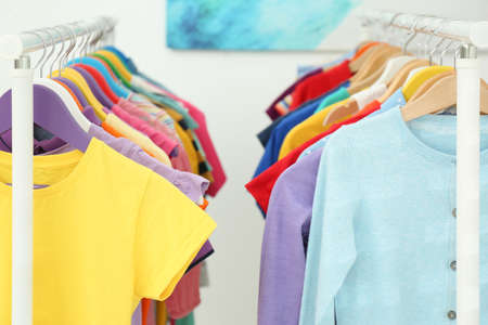 Different child's clothes hanging on racks indoors, closeup
