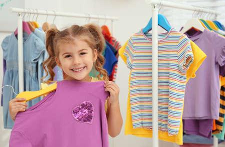 Little girl choosing clothes on rack indoors Stockfoto