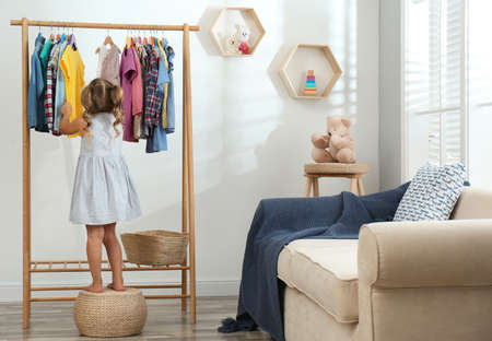 Little girl choosing clothes on rack in living room