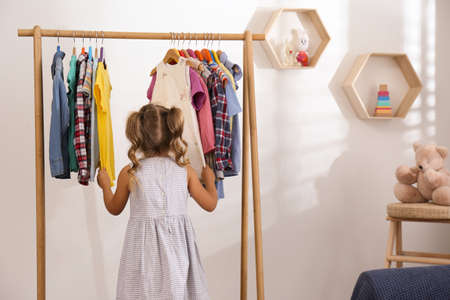 Little girl choosing clothes on rack in room Stockfoto