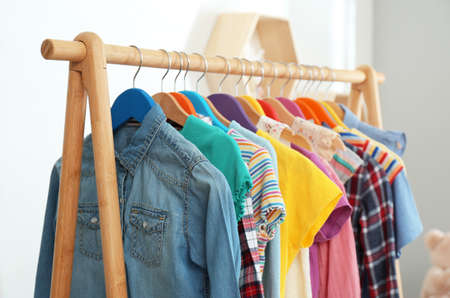 Different child's clothes hanging on rack indoors, closeup