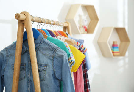 Different child's clothes hanging on rack indoors, closeup. Space for text