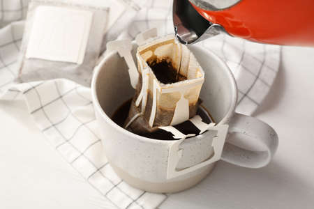 Pouring hot water into glass cup with drip coffee bag on white wooden table, closeup