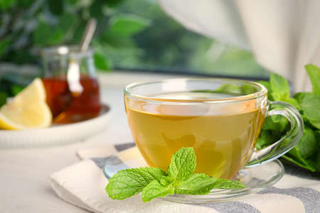 Fresh green tea with mint leaves on table