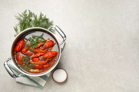 Fresh delicious crayfishes in pot on light gray table, flat lay. Space for text