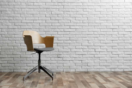 Comfortable office chair near white brick wall indoors. Space for text