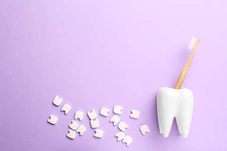 Small plastic teeth and wooden brush in holder on violet background, flat lay. Space for text Banco de Imagens