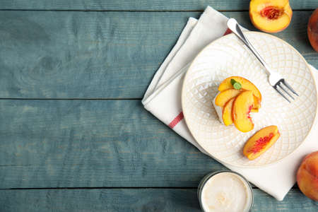 Delicious peach dessert on blue wooden table, flat lay. Space for text