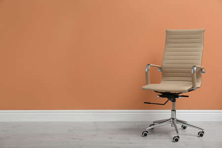 Modern office chair near orange coral wall indoors. Space for text Stockfoto