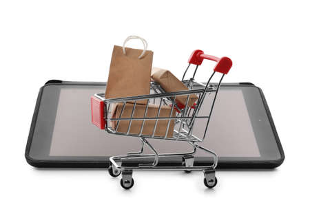 Internet shopping. Small cart with boxes and bag near modern tablet on white background