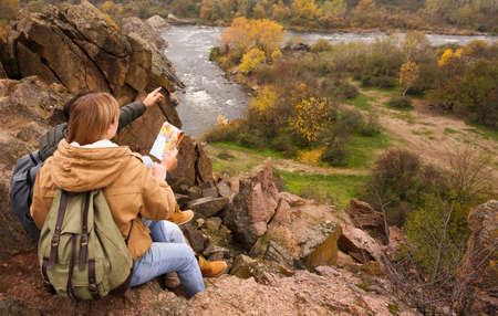Couple of travelers with backpacks and map sitting on steep cliff. Autumn vacation