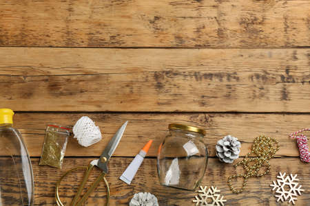 Instruments and materials for snow globe on wooden table, flat lay. Space for text