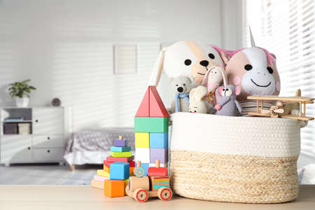Set of different cute toys on wooden table in children's room. Space for text Stockfoto