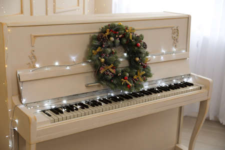 White piano with fairy lights and decorative wreath indoors. Christmas music
