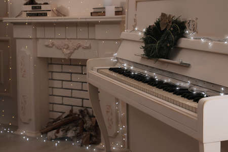 White piano with fairy lights and wreath near decorative fireplace indoors. Christmas music