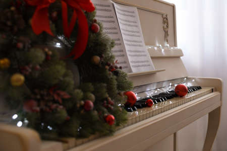 White piano with festive decor and note sheets indoors, closeup. Christmas music Stock Photo
