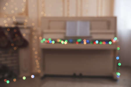Blurred view of white piano with fairy lights indoors. Christmas music Stock Photo