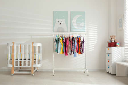 Different clothes hanging on rack in bedroom