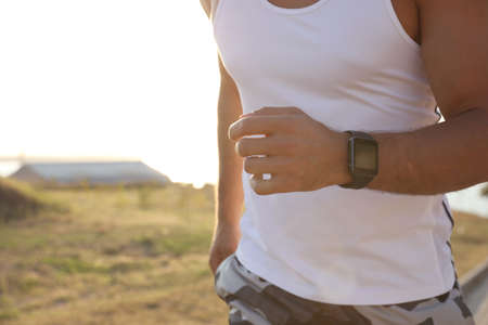 Man with fitness tracker running outdoors, closeup