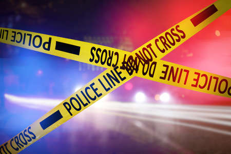 Yellow law enforcement tape isolating crime scene. Blurred view of city street, toned in red and blue police car lights