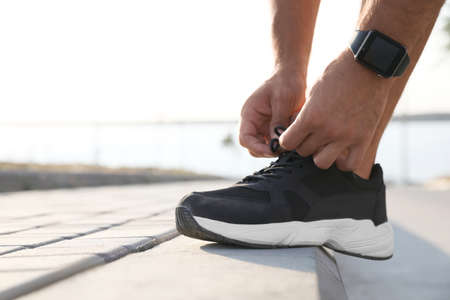 Man with fitness tracker tying shoelaces outdoors, closeup. Space for text