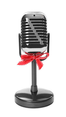 Retro microphone with red bow isolated on white. Christmas music