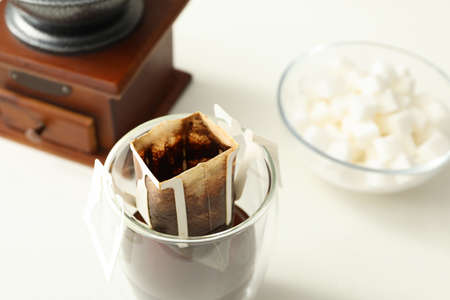 Glass with drip coffee bag on white table, closeup Foto de archivo