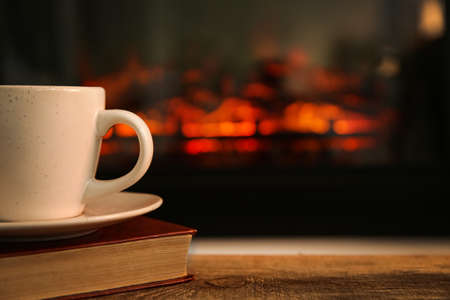 Cup with hot drink and book on table against fireplace, space for text