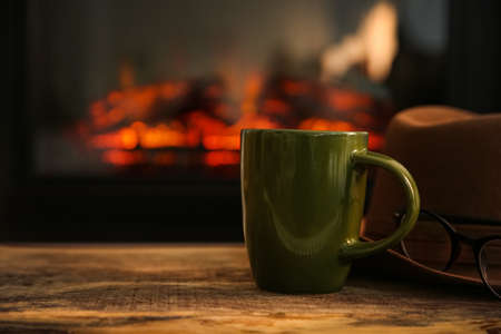 Green cup with hot drink on wooden table against fireplace, space for text