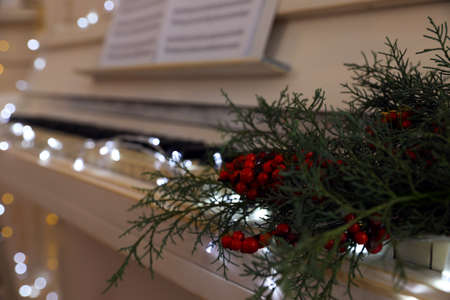 Fir branches with berries on piano keys indoors, space for text. Christmas music
