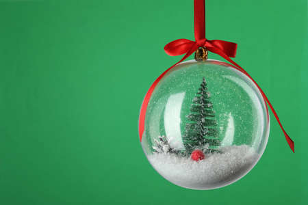 Beautiful Christmas snow globe hanging on green background, closeup. Space for text