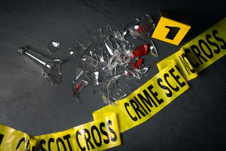 Broken bottle with blood, yellow tape and evidence marker on black slate background, flat lay. Crime scene