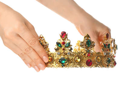 Woman holding beautiful golden crown on white background, closeup. Fantasy item
