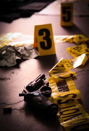 Composition with gun on black slate table, closeup. Crime scene