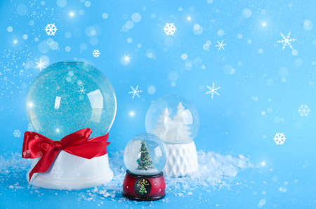 Beautiful Christmas snow globes on light blue background, bokeh effect. Space for text