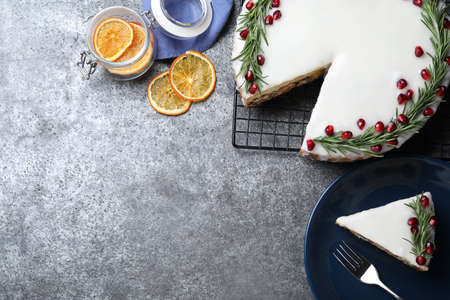 Flat lay composition with traditional Christmas cake on gray table. Space for text